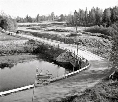 53. Gamla landsvägen vid kyrkan. I bakgrunden pågår bygget av nya landsvägen ( Riksväg 9 senare E18 ).  Foto : Fritz Arenö / Årjängs kommuns bildbank