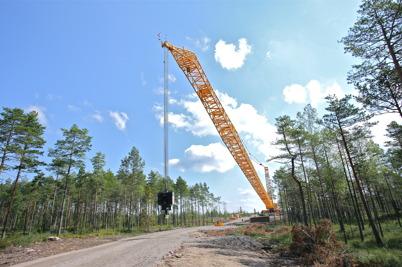 9 juli 2014 - Den stora byggkranen lyfte sin  långa arm mot skyn, för lyft upp till 124 meter.