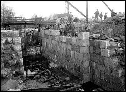 Sprängningsarbetet vid övre slussen är klart. Stensättningen för en av slussportarna och det nya brofästet pågår. I bakgrunden syns läkarbostaden Tomtebo.