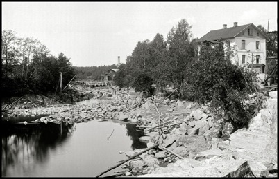 En tillfällig vattenbarriär har byggts vid Sanamons sågverk, för att möjliggöra torrläggning av kanalen i samband med byggandet av övre slussen. Huset till höger är läkarbostaden Tomtebo.