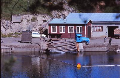 Med tiden förändrades arbetet med transport av timmer, från flottning till transport på lastbilar. På bilden tippar en virkeslastbil sågtimmer vid Bruket i Töcksfors / Foto : Uno Brander