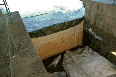 En tillfällig träbarriär stoppar vattnet när slussporten är borta / Foto : Walter Christofferson - 20 mars 2006