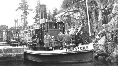 Bogserbåten Töcksfors passerar nedre slussen i Töcksfors.