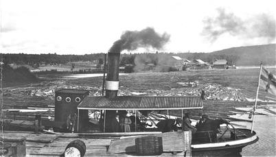 Bogserbåten Töcksfors i Östervallskog. I bakgrunden syns snickerifabriken/ Foto : okänd.
