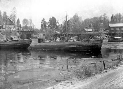 Lastbåtarna TÖCKSFORS och HÅNSFORS i hamnen vid Töcksfors Bruk på 1930-talet. Båtarna gick med gods till Göteborg.  Foto : Axel Gunnar ödvall / Årjängs kommuns bildbank.