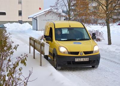 25 januari 2010 - Brevbäraren sorterar posten i brevlådor utanför husen.