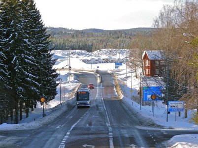 2 mars 2010 - Swebus Express, på  väg från Oslo till Stockholm, passerar vägkorsningen vid Töcksmarks kyrka. I bakgrunden syns området där Töcksfors handelspark skall byggas