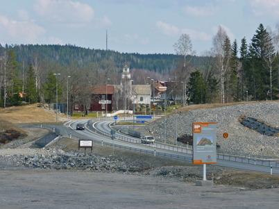 4 april 2010 - Västra infarten till Töcksfors på nya E18, vid området där Töcksfors handelspark skall byggas. I bakgrunden syns Turistgården, Töcksmarks kyrka, församlingshemmet och äldreboendet Solgården.