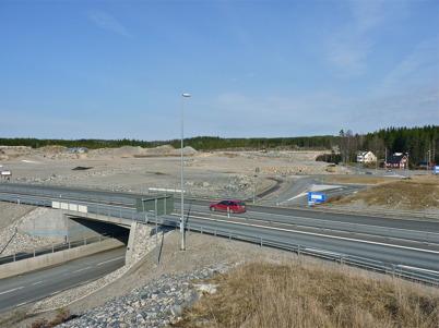 4 april 2010 - Området där Töcksfors handelspark skall byggas ligger intill nya E18. I bakgrunden syns rondellen där Östervallskogsvägen och gamla E18 från Hån ansluter.