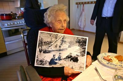 Thora håller ett fotografi taget 1912 då Kanalen Stora Lee - Östen byggdes. Thora´s far Georg Henriksson, längst till vänster på fotografiet, har paus i arbetet med muddring i Strömmerkanalen. Thora föddes 1915 det år då kanalen invigdes.
