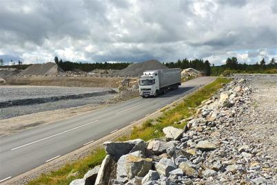28 juli 2010 - Gamla E18 går genom området där Töcksfors handelspark skall byggas. Långtradarna måste fortfarande åka gamla E18 till tullstationen i Hån för deklarering av gods, eftersom det ännu inte har byggts ny tullstation vid nya E18.