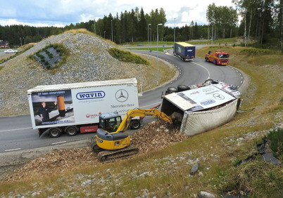 2 augusti 2010 - Lastbilsolycka i kurvan före påfarten till E18 vid Nordmarksstugan. Lasten av träflis lossas med hjälp av en grävmaskin.