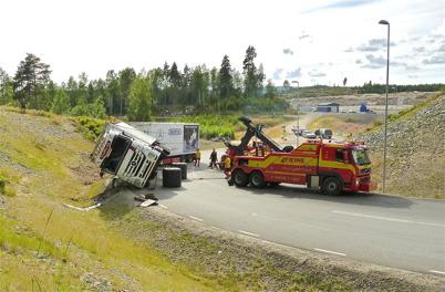 2 augusti 2010 - Lastbilsolycka i kurvan före påfarten till E18 vid Nordmarksstugan. Två tunga bärgningsbilar drar upp lastbilen.