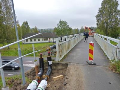 23 september 2010 - HL Energi bygger ut fjärrvärmenätet till fritidsgården Högalid, skolan, sporthallen och den nya förskolan. Här dras fjärrvärmerören på utsidan av gång- och cykelbron över E18 vid församlingshemmet.