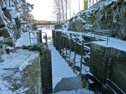 7 december 2010 - Slussportarna vid nedre slussen skall transporteras till en mekanisk verkstad i Stenungsund för renovering. Slussen kommer därför att stå utan portar under vintern. En träbarriär håller emot vattnet.
