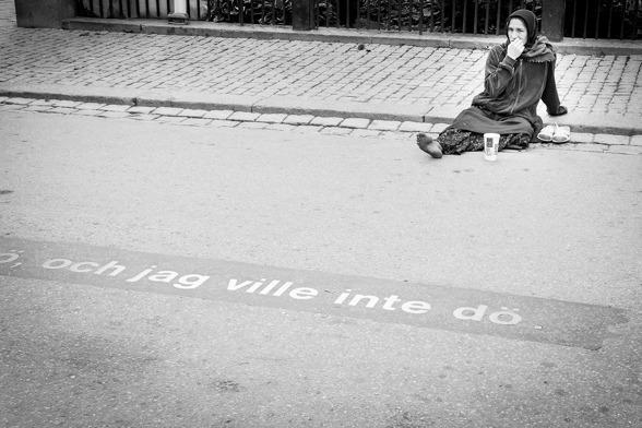 Drottningatan i Stockholm. August Strindbergs rader ses infasade i asfalten. Kvinnan är säkert ovetandes om textens träffsäkerhet. Copyright Thommy Jakobsson / klickbar bild