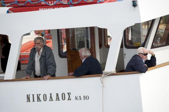 Uppgivna grekiska män. Välfärden kantrar.