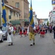 Fanor / drillflickor / manskör och musikkår på väg till Nationaldagsfirande i Stadsparken.