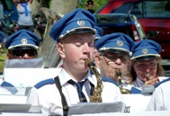"""En av de yngsta musikanterna Joel Nilsson på saxofon.  I bakgrunden Tomas Åstrand """"Tuba"""".  Anders Ålstam """" Barytonsaxofon"""".  Eva Larsson """"Trumpet"""" ."""