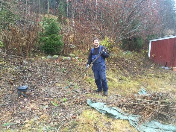 Uffe in action rensar sly och gräs i slänten framför huset. I bakgrunden ser man förrådet