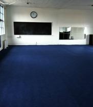 Inomhushallen med matta, spegelvägg samt högtalaranläggning