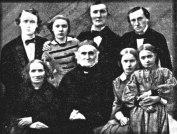 Familjeporträtt - Elias och Christina Fries och sex av deras barn. Fotografi taget sannolikt år 1859 i ett av växthusen i Uppsala botaniska trädgård.