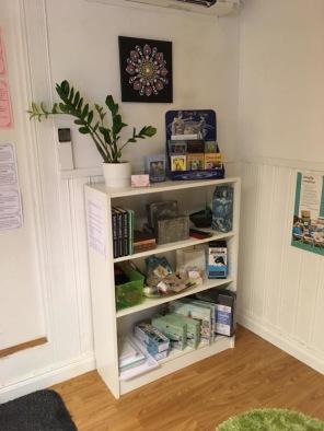 En liten produkthylla med Encaustic Art material, rökelser, tarot- och änglakort....