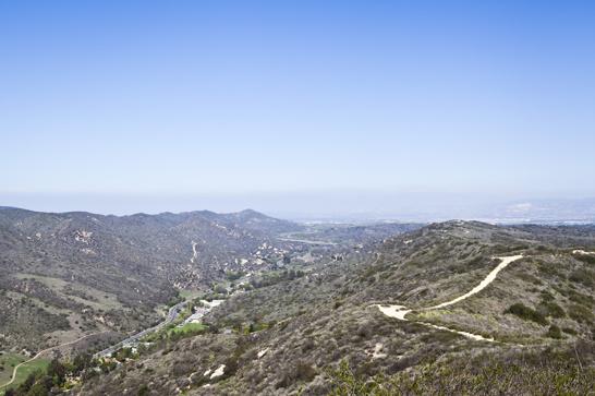 Höga berg och djupa dalar. Här syns den väg som går från Laguna Beach, genom bergen och senare tar vid de större motorvägarna utanför staden. På så sätt skapas det exkluderade, småskaliga samhället i dalens famn.