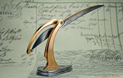 "The Trebuchet -  A Damasteel ""scalpel"" in an adjustable Bronze/Damasteel stand."