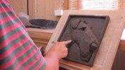 Först kavlar jag ut leran till en platta som får torka något. Därefter börjar jag skulptera hunden, i detta fall en airedaleterrier