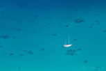 A lonely sailboat in the lagoon of Bora Bora, Tahiti