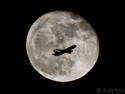 A Boeing 737 passes the full moon