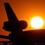 An old trijet DC10 parked during the setting sun