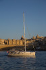 Sailboat infront of the walls around Valletta, Malta