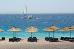 Dhërmi beach with aligned sun beds and parasols