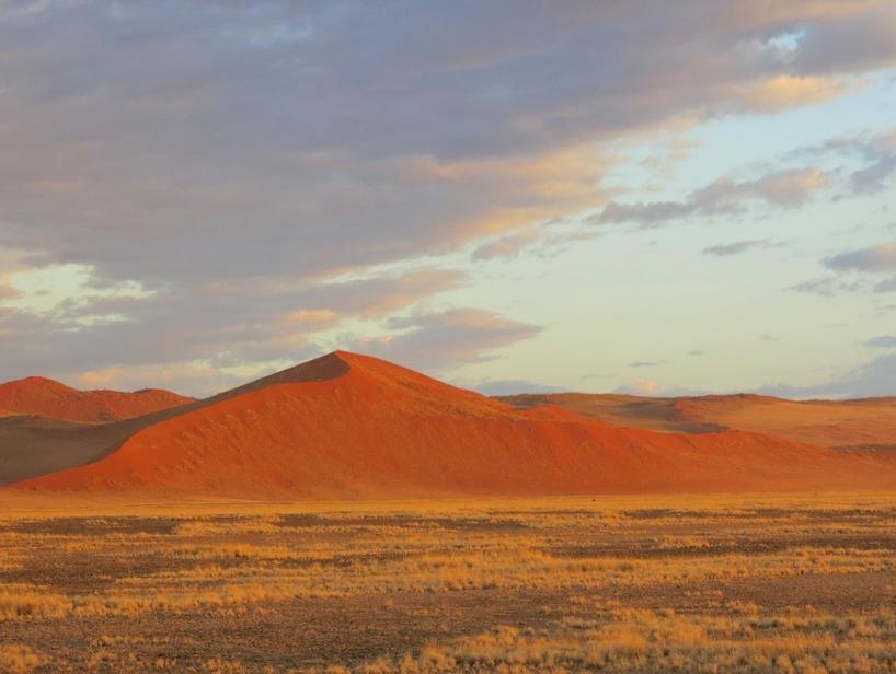 Morgonen därpå och vi har utsikt över dessa röda sanddyner när solen reser sig över horisonten och färgar allt ännu mer rött...