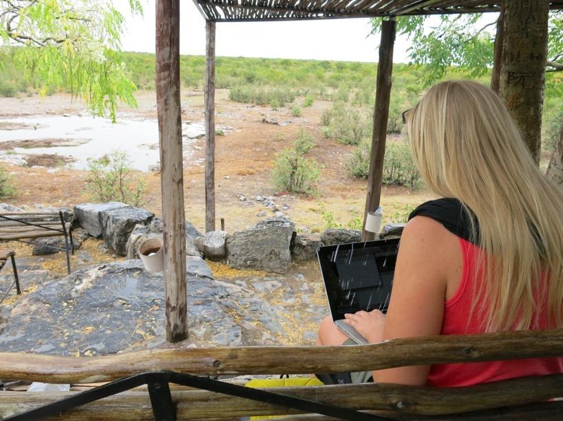 Sussie sitter framför Lodgens egna vattenhål och skriver på inlägget!