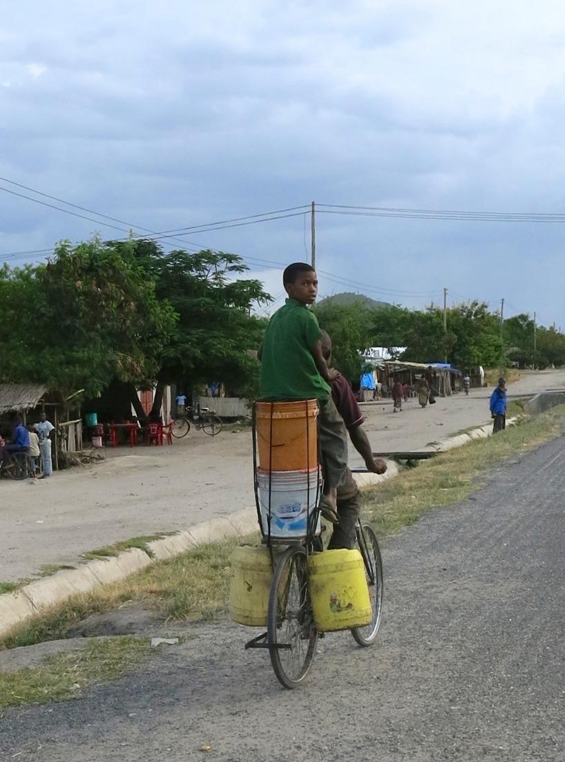 Multifunktionell cykel! Pappa hämtar både vatten och skjutsar sin son!