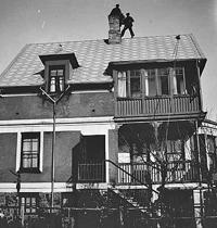 Två sotare står uppe på Afrikahusets tak. Den 22 april 1930.
