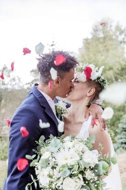 Nygift brudpar i rosenblad. Blomkrans i håret. Bröllopsfotograf Åsa Lännerström