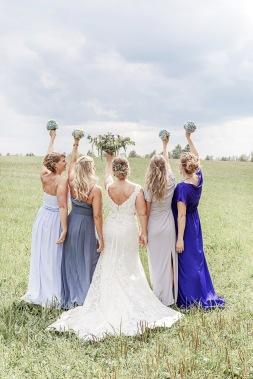 Bröllopsfotografering på en äng vid uddetorps säteri, bruden med sina brudtärnor och brudbuketter. Bröllopsfotograf Åsa Lännerström