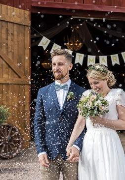 Nygift brudpar med riskastning, uddetorps säteri. Bröllopsfotograf Åsa Lännerström