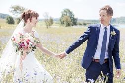 Bröllopsfotografering av brudpar i ett blåklintsfält. Bröllopsfotograf Åsa Lännerström