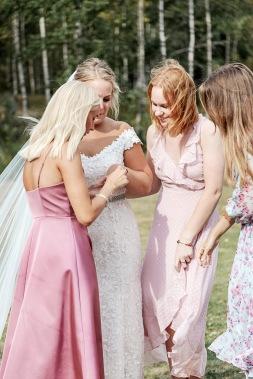 Vänninor tittar på den nygifta brudens vigselring. Bröllopsfotograf Åsa Lännerström