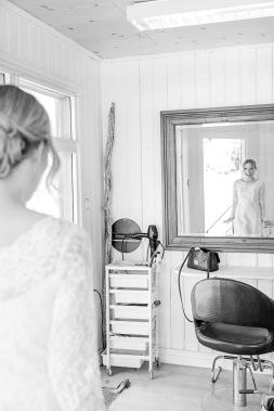Nysminkad brud tittar sig i spegeln, Lysekil. Bröllopsfotograf Åsa Lännerström
