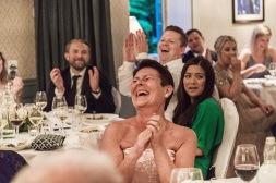 Gäst på bröllopsfesten skrattar påt tal. Bröllopsfotograf Åsa Lännerström