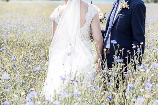 Brudpar ståendes i ett blåklintsfält. Bröllopsfotograf Åsa Lännerström