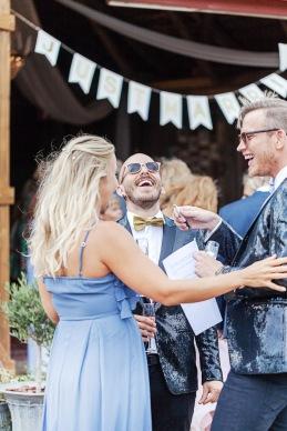 Bröllopsgäster pratar och skrattar på bröllopsfest på uddetorps säteri. Bröllopsfotograf Åsa Lännerström