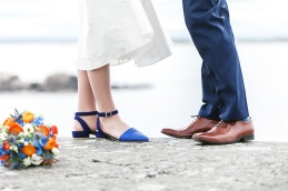Blå brudskor och brudbukett i blå och orange färger.  Bröllopsfotograf Åsa Lännerström