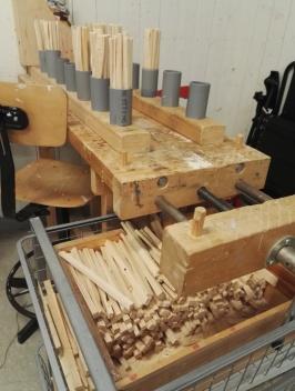 Vedgruppen har en lyxig vedbod. Här tillverkas förutom brasved, egna braständare. Rören hjälper till så det blir lika mycket i alla.
